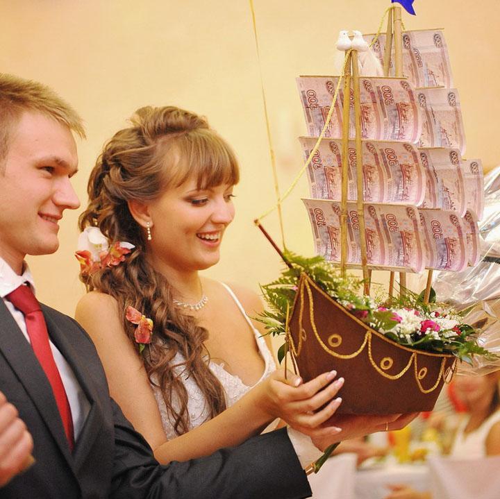 молодожены с свадебным подарком,корабль с парусами из денежных копюр